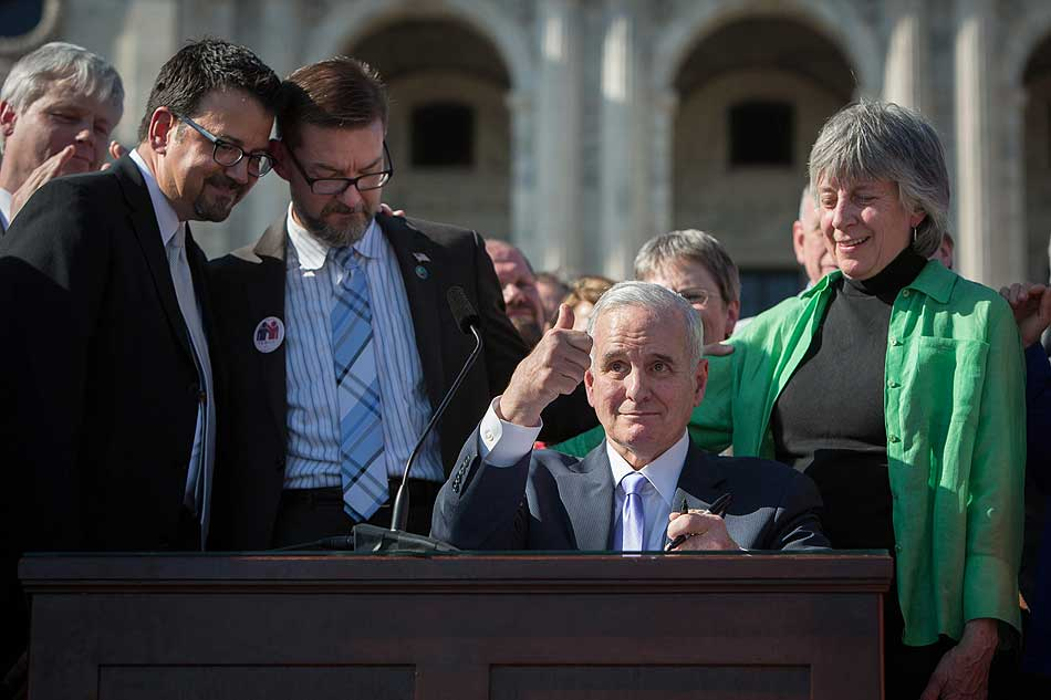 Minnesota's old, white, male governor gives a thumbs-up after signing the bill.