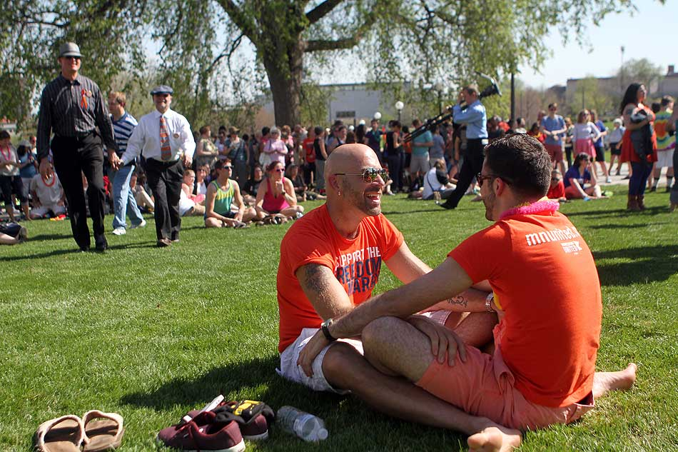 Two men sit close together on the grass, facing each other, hands on each other's thighs, with a little bit of space between them and the standing crowds around them, a lovely intimate moment in such a public place.
