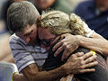A couple embraces during a memorial service