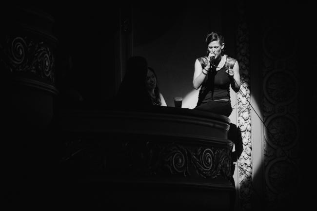 Dessa performing on a balcony at the Fitzgerald Theater