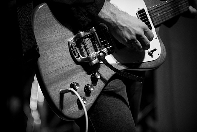 Bryce Dessner plays a chord on his 1965 Gibson Firebird during sound check. August 6, 2013.