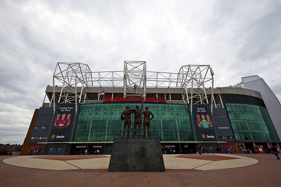 """Old Trafford, the home stadium of Manchester United. In the foreground is the statue of the club's """"holy trinity"""" of George Best, Denis Law and Bobby Charlton."""