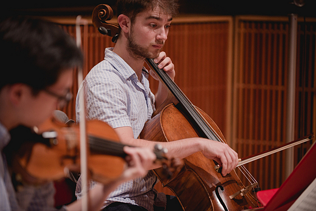 Cellist Camden Shaw of the Dover Quartet performs in the studios at American Public Media. Violinist Bryan Lee is in the foreground.
