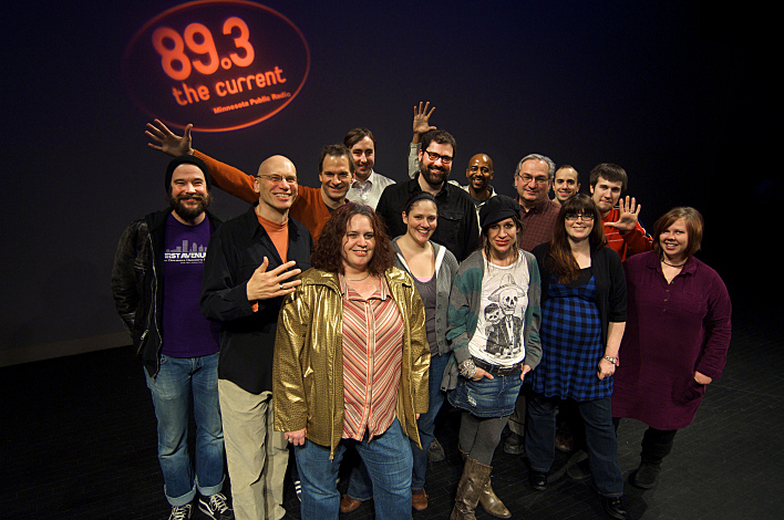 The staff of The Current photographed in 2009; front: Barb Abney, Lindsay Kimball, Mary Lucia, (former music director) Melanie Walker, Jill Riley; middle: David Campbell, Mark Wheat, Jim McGuinn, Steve Seel, Michael DeMark, Mac Wilson; back: Matt Perkins, Derrick Stevens, David Safar.