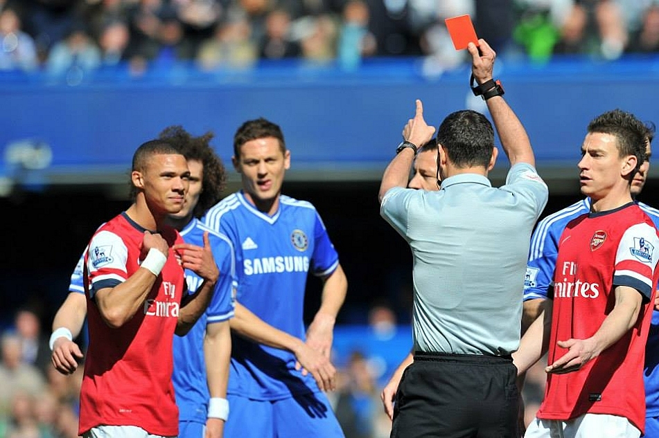 Arsenal's English defender Kieran Gibbs (L) is incorrectly sent off by referee Andre Marriner after Alex Oxelaide-Chamberlain handballs in the area.