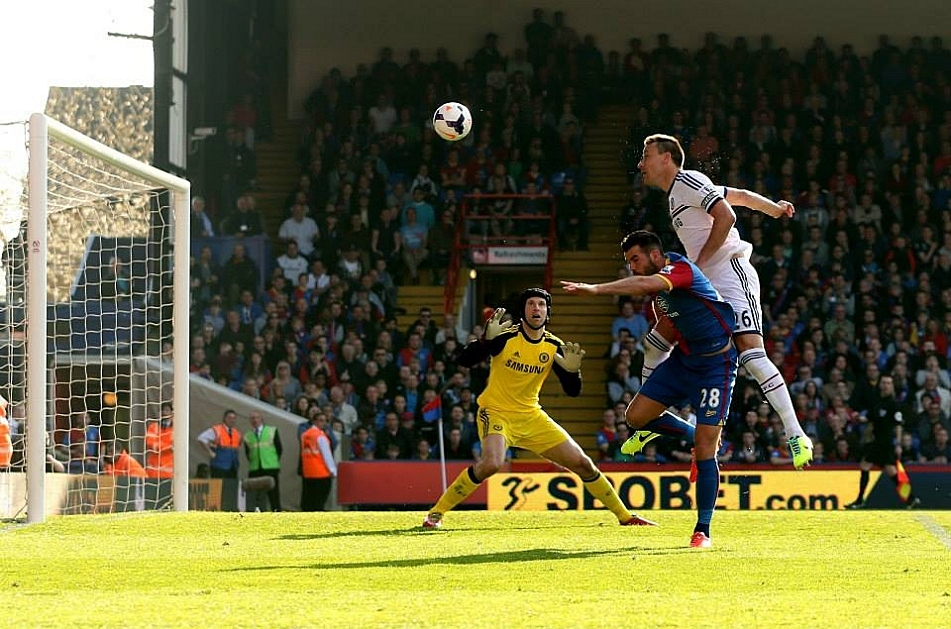 John Terry (R) of Chelsea is pressurised by Joe Ledley of Crystal Palace and heads the ball over his goalkeeperPetr Cech to open the scoring with an own goal.