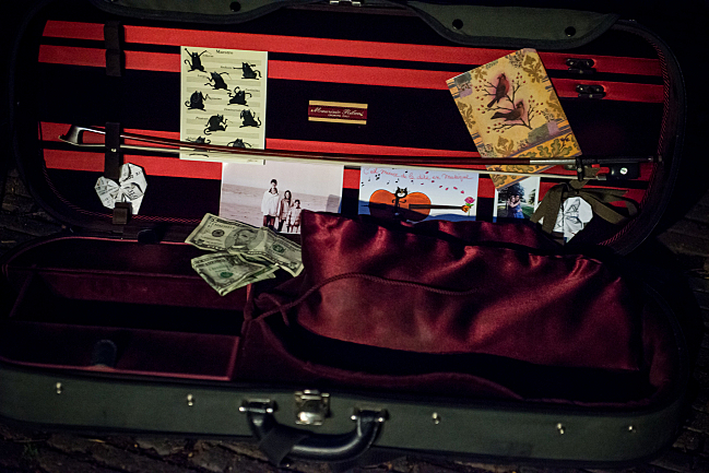 The inside of Chloe Thominet's viola case collects both mementos and change from playing in public