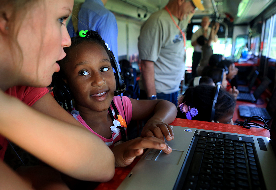 Third-grader Rananjea Griffen works with volunteer intern Elizabeth Carpenter on the Rock 'n' Read Project bus at Hmong International Academy in Minneapolis, Minn. Wednesday, July 23, 2014. The mobile computer lab is used to help students improve reading skills by singing aloud with music-based software.