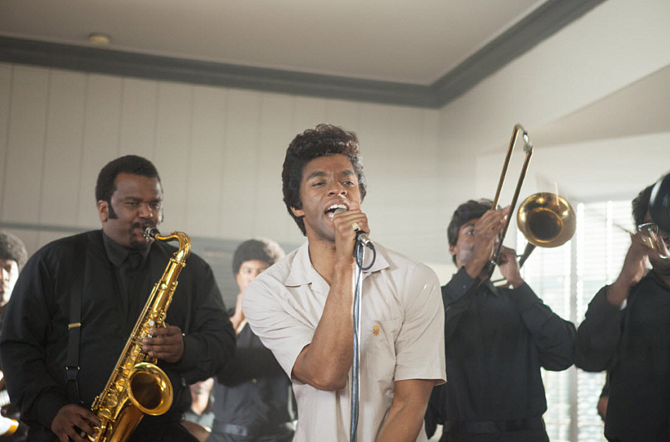'Get On Up' stars Chadwick Boseman as James Brown. Craig Robinson (at left) plays saxophonist Maceo Parker.
