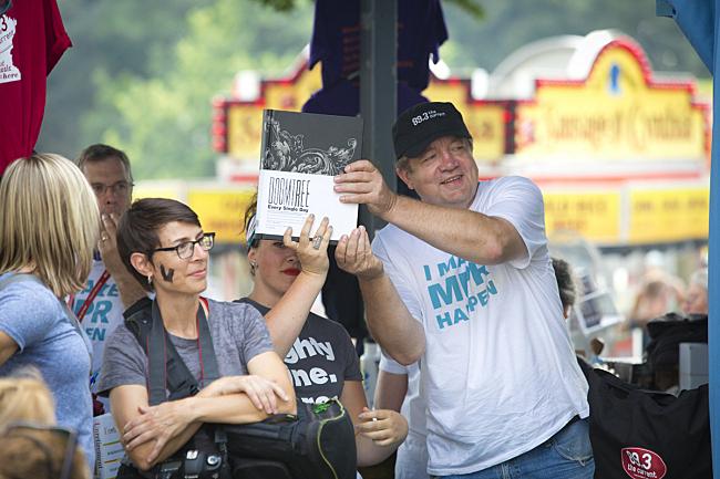 MPR volunteers hold up the massive six pound Doomtree photo album.
